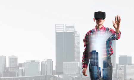 futuristic city: Young man with virtual reality headset or 3d glasses over cityscape background