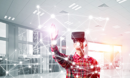 Young man with virtual reality headset or 3d glasses over connection background. Mixed media Reklamní fotografie