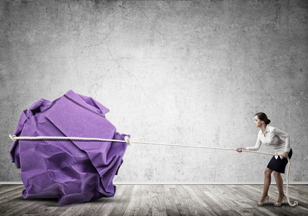 cement solution: Young woman making huge paper ball move Stock Photo