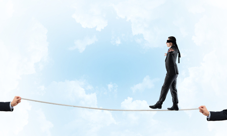 Businessman with blindfolder on eyes walking on rope over sky background
