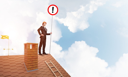 suburbian: Young businessman with roadsign in hand standing on brick roof. Mixed media Stock Photo