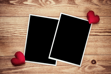old photograph: Blank photo frame and love hearts on wooden table Stock Photo