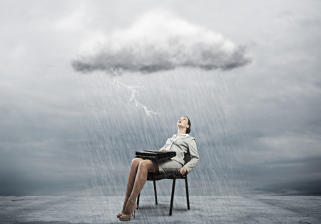 joblessness: Young businesswoman with suitcase sitting on chair under rain Stock Photo
