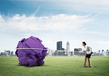 Young woman outdoors making huge paper ball move Stock Photo