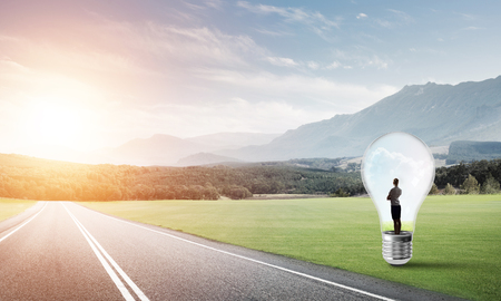 trapped: Young businesswoman trapped inside of light bulb on asphalt road Stock Photo