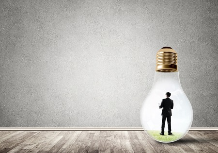 cement solution: Businessman inside of light bulb in empty concrete room