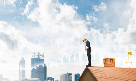 suburbian: Young businessman in suit and helmet on roof edge. Mixed media Stock Photo