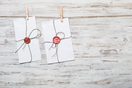 Envelope hanging on rope on wooden background