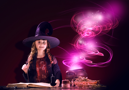Little Halloween witch reading conjure from magic book above pot Stock Photo