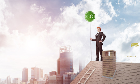 Young caucasian businessman standing on house roof and holding go green sign. Mixed media