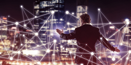 futuristic city: Back view of businessman against night cityscape working with social connection media concept Stock Photo