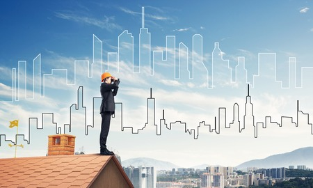 mixed media: Young businessman in suit and helmet on roof edge in search of something new. Mixed media