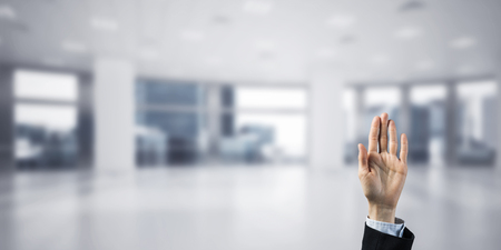 Close of businesswoman hand touching screen with palm and office at background Stock Photo