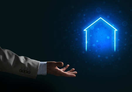 Businessman hand presenting glowing home icon or symbol Banco de Imagens