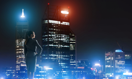 night vision: Rear view of elegant businesswoman viewing lights of night city
