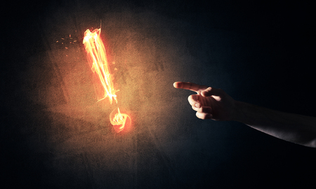 indicate: Hands reaching each other and fire glowing exclamation mark Stock Photo
