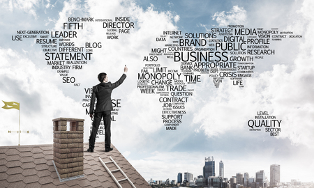 Young businessman standing on house roof and writing business related words. Mixed media Stock Photo