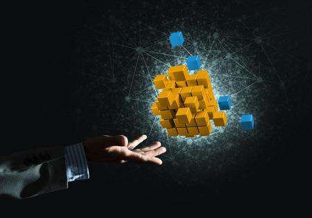 technology symbols metaphors: Close of businessman hand holding cube figure as symbol of innovation, mixed media Stock Photo
