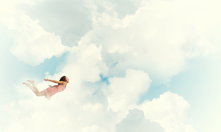 Young woman flying high in blue sky 版權商用圖片 - 80986427