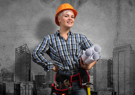 architect drawing: Engineer woman with blueprints and sketches of construction project on wall