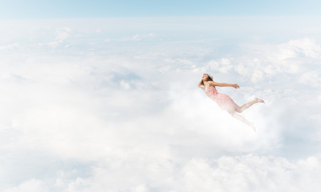 Young woman flying high in blue sky 版權商用圖片 - 81080881