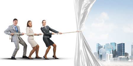 strong: Three businesspeople pulling white blank fabric with rope Stock Photo