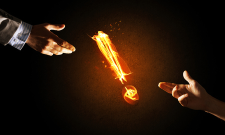 Hands reaching each other and fire glowing exclamation mark Stock Photo