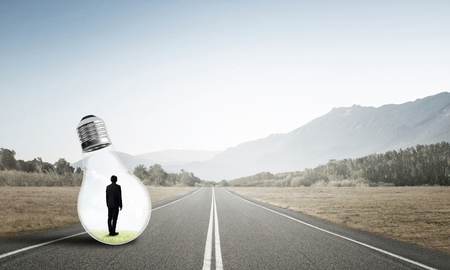 trapped: Young businessman trapped inside of light bulb on asphalt road