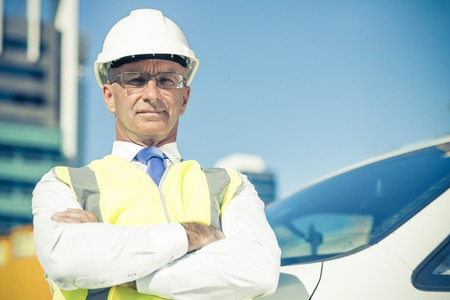 architect: Confident construction engineer in hardhat with arms crossed on chest