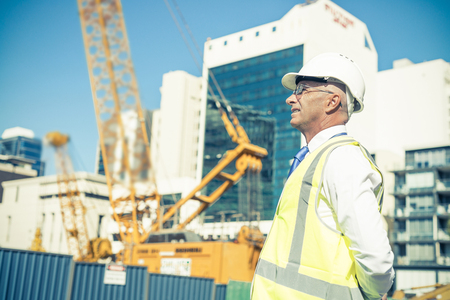 architect: Engineer man in helmet and jacket controlling outdoor construction site