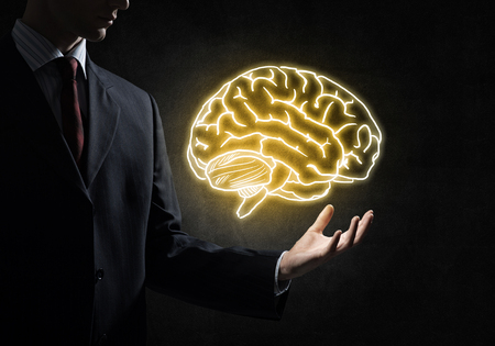 Close up of businessman hand holding brain in palm. Stock Photo