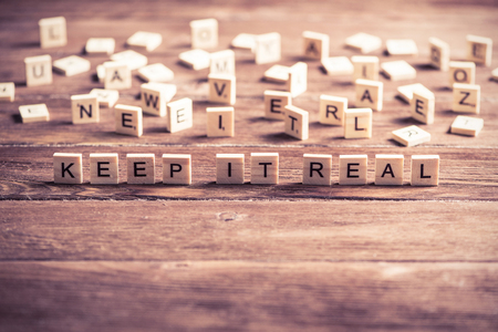 keep it real phrase collected of wooden elements with the letters Stock Photo