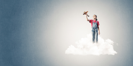 careless: Cute kid girl standing on cloud and playing with airplane toy Stock Photo
