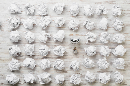 Many balls of crumpled paper and light bulb among them Stock Photo