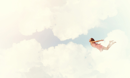 Young woman flying high in blue sky 版權商用圖片 - 79040718