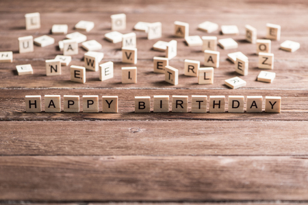 Alphabet letters on wooden pieces collected to word happy birthday