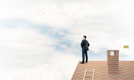 Jonge bepaald zakenman staan met de rug op de dak van het huis en kijkt weg. Gemengde media