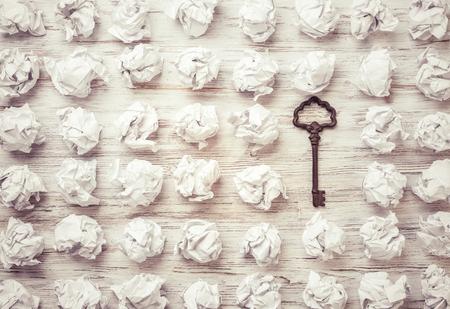 しわくちゃの紙の多くのボールの中でビンテージのキー