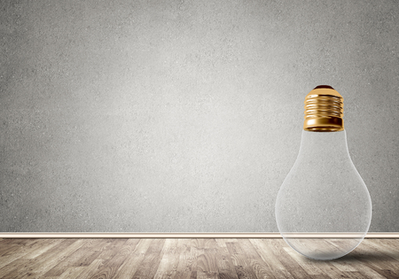 Glass light bulb in concrete empty room
