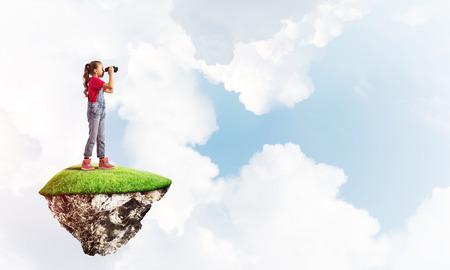 Leuke lachende meisje zittend op drijvende eiland hoog in de lucht