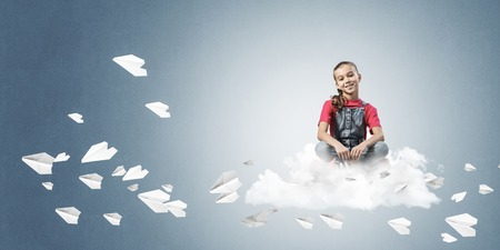 Cute kid girl sitting on cloud and paper planes flying around Reklamní fotografie
