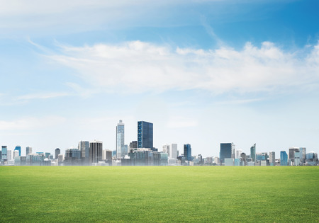 Background image with modern cityscape blue sky and green spring field Stok Fotoğraf - 81013655