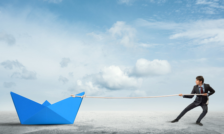 Successful businessman pulling with rope paper boat Stock Photo