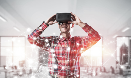 modified: Young man with virtual reality headset or 3d glasses over connection background. Mixed media Stock Photo
