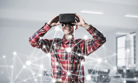 Young man with virtual reality headset or 3d glasses over connection background. Mixed media Stock Photo