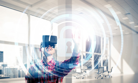 futuristic interior: Guy wearing checked shirt and virtual headset working with media screen panel Stock Photo