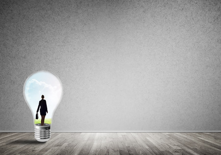 cement solution: Businesswoman inside of light bulb in empty concrete room