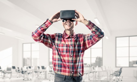 mediated: Young man with virtual reality headset or 3d glasses playing game in room
