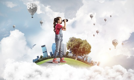 Cute kid girl on city floating island looking in binoculars Stock Photo