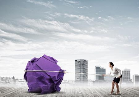 巨大な紙のボールの動きを作る屋外の若い女性 写真素材